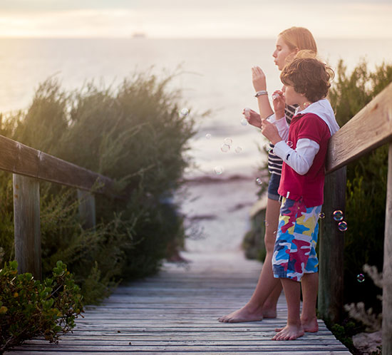 kids blowing bubbles on a beach
