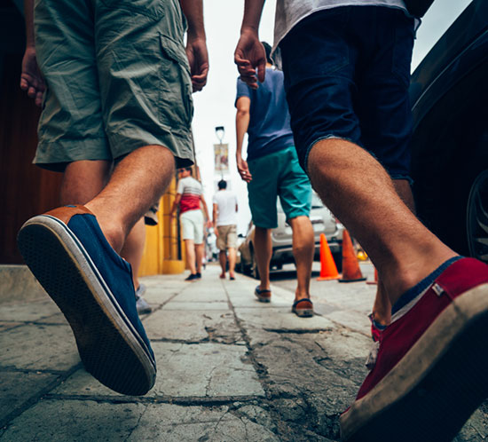 Low angle shot of the feet of some men friends walking down a street